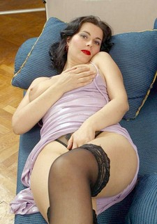 Mature adorable chick is posing naked on the couch