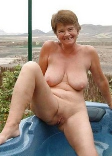 Smiling naked granny posing