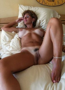 Tanned milf lady on the bed - exciting amateur porn shots